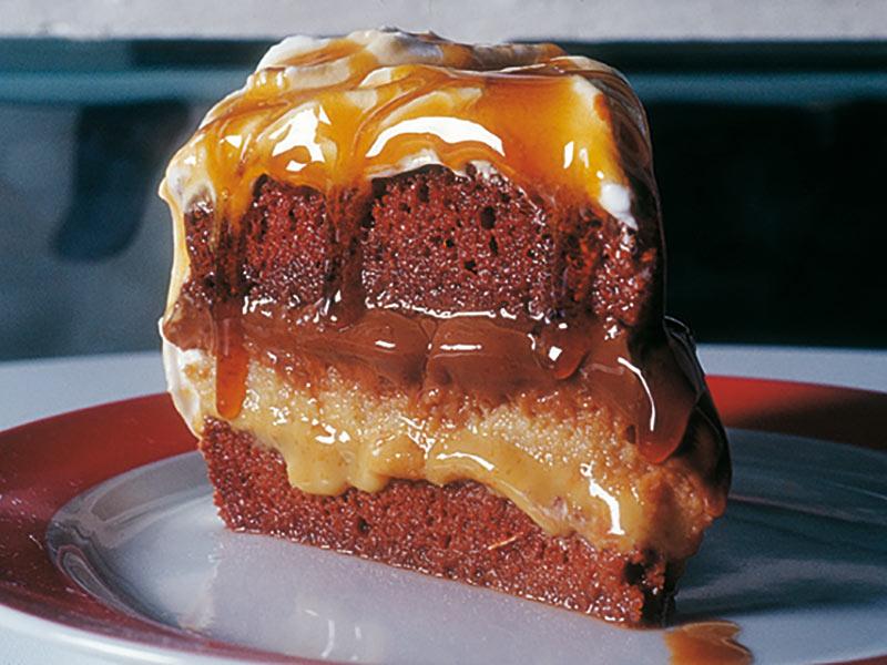 Bolo branco e de chocolate, recheado com creme brigadeiro e doce de leite condensado coberto com marshmallow e calda de caramelo.