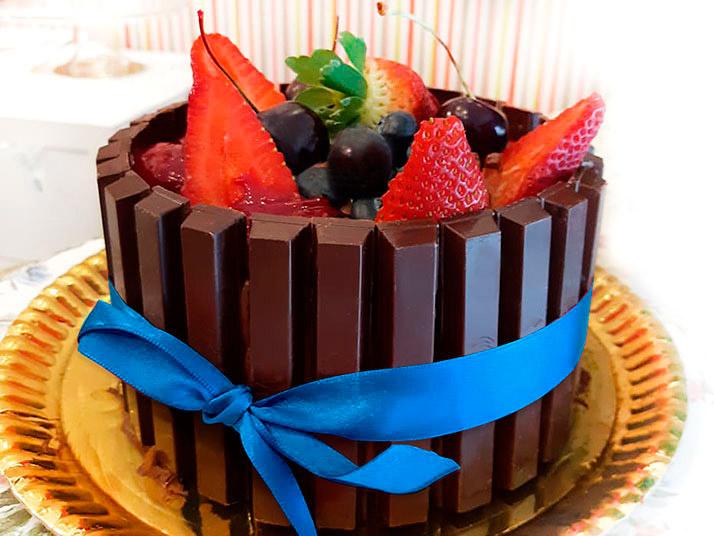 Bolo dos Pais: bolo de chocolate, mousse de chocolate 60% cacau, envolto por barrinhas de Kit Kat e coberto com frutas vermelhas.